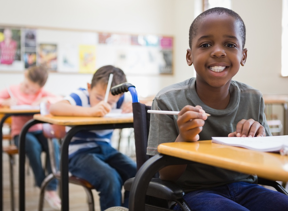 Disabled pupil smiling at camera in classroom at the elementary school.jpeg